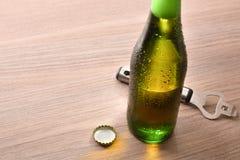 Groene fles met alcoholische drank op houten opgeheven lijst stock foto's