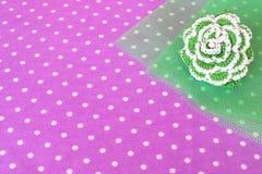 Groene gebreide bloem op een groene en purpere achtergrond Stock Afbeeldingen