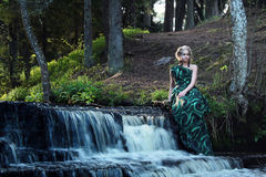 Groene geklede jonge nimfvrouw dichtbij waterval in het bos Stock Afbeeldingen