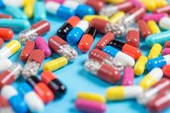 Groene, gele, rode en roze pillen of capsules op een blauwe achtergrond stock foto's