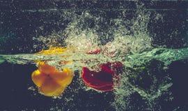 Groene Gele Rode groene paprika'sdaling in het water met plons Royalty-vrije Stock Afbeeldingen