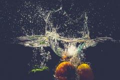 Groene Gele Rode groene paprika'sdaling in het water met plons Stock Foto