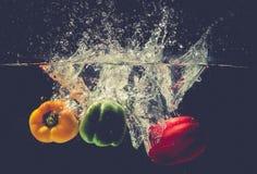 Groene Gele Rode groene paprika'sdaling in het water met plons Stock Afbeelding