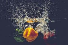 Groene Gele Rode groene paprika'sdaling in het water met plons Royalty-vrije Stock Foto's