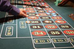 Groene gevoelde roulettelijst met spelers die weddenschappen plaatsen Royalty-vrije Stock Afbeeldingen