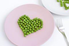 Groene gevormd erwtenhart, roze plaat en een vork op witte lijst St Valentine ` s dagconcept stock fotografie
