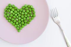 Groene gevormd erwtenhart, roze plaat en een vork op witte lijst St Valentine ` s dagconcept stock afbeeldingen