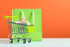 Groene giftdoos in boodschappenwagentje en zak Stock Foto's