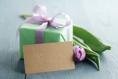 Groene giftdoos met purpere boog en tulp op blauwe houten achtergrond met lege groetkaart Royalty-vrije Stock Fotografie