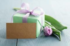 Groene giftdoos met purpere boog en tulp op blauwe houten achtergrond met lege groetkaart Royalty-vrije Stock Foto