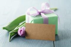 Groene giftdoos met purpere boog en tulp op blauwe houten achtergrond met lege groetkaart Stock Fotografie