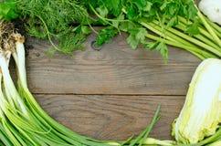 Groene groenten en kruiden op houten plaat Stock Afbeeldingen