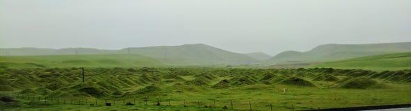 Groene het uitzicht rollende heuvels van de panoramafantasie op nevelige dag stock fotografie