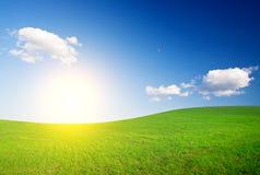Groene heuvel onder blauwe bewolkte hemelwhit zon Stock Foto's