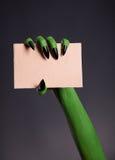 Groene huidhand met scherpe spijkers die leeg stuk van cardboar houden Stock Afbeeldingen