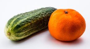 groene komkommer en oranje mandarin op een witte achtergrond Stock Afbeeldingen