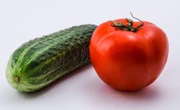 groene komkommer, rode tomaat op een witte achtergrond Stock Foto's