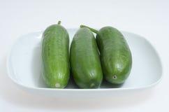 Groene komkommers op een witte plaat Stock Afbeeldingen