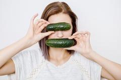 Groene komkommers ter beschikking het meisje houdt komkommers Stock Fotografie