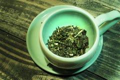 Groene kruidthee in een kop op houten lijst Groene theebladen voor gezondheid stock foto's