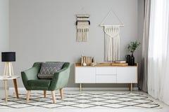 Groene leunstoel op gevormd tapijt dichtbij lijst met lamp in halve noot stock afbeelding