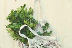 Groene nul afvallevensstijl, witte milieuvriendelijke opnieuw te gebruiken koordzak met verse groene peterselie voor plantaardige royalty-vrije stock foto