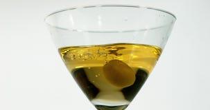 Groene Olijf, oleaeuropaea, die in een Glas Vermouth vallen, stock footage