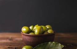 Groene olijven in een ceramische kom op een houten achtergrond Stock Foto's