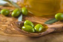 Groene olijven en olie op een houten lepel stock afbeelding