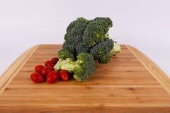 Groene organische broccolikroon en van de bloemen zoete kers tomaten op een licht hout cuttingboard Stock Foto