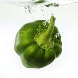 Groene paprika die in water wordt gelaten vallen Stock Afbeelding