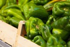 Groene paprika in een houten mand bij markt Stock Afbeelding