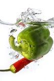 Groene paprika en rode Spaanse peper die in water wordt gelaten vallen Stock Afbeeldingen
