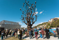 Groene park en mensen met kinderen die op de Boom van het ijzerbeeldhouwwerk letten Stock Foto's