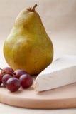 Groene peer, kaasBrie, rode druiven aan boord Stock Foto's