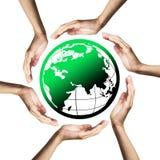 Groene planeet (Aarde) die door handen wordt omringd Royalty-vrije Stock Afbeelding