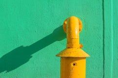 Groene pleistermuur met gele pijp Stock Afbeelding