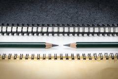 Groene potloden tussen notaboeken Stock Foto's
