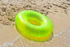 Groene reddingsboei op strand Stock Afbeelding