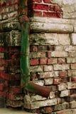 Groene rioolbuis bij bakstenen muur Royalty-vrije Stock Foto