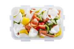 Groene rode gele koele paprika en ui in plastic dooscontainer Stock Fotografie