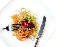 Groene rode gele noedels met ketchup op een witte plaat met vork Stock Fotografie