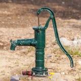 Groene roestige handwaterpomp stock afbeeldingen