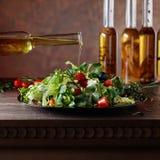 Groene salade met olijfolie het gieten van een kleine fles Royalty-vrije Stock Fotografie