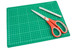 Groene scherpe mat met snijder en Schaar op witte achtergrond Royalty-vrije Stock Fotografie