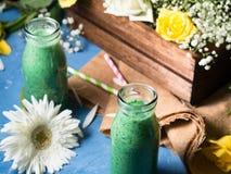 Groene smoothie in glasflessen met bloemen Stock Afbeelding