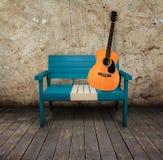 Groene stoel en akoestische gitaar in een grungeruimte Stock Afbeeldingen