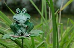 Groene stuk speelgoed kikker op grasachtergrond royalty-vrije stock afbeeldingen