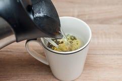 Groene thee in een kop op een houten lijst royalty-vrije stock afbeeldingen