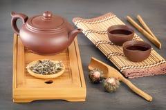 Groene thee en attributen voor theeceremonie - een ceramische theepot, de koppen, een zeef, de eetstokjes en het pincet worden ge royalty-vrije stock afbeelding